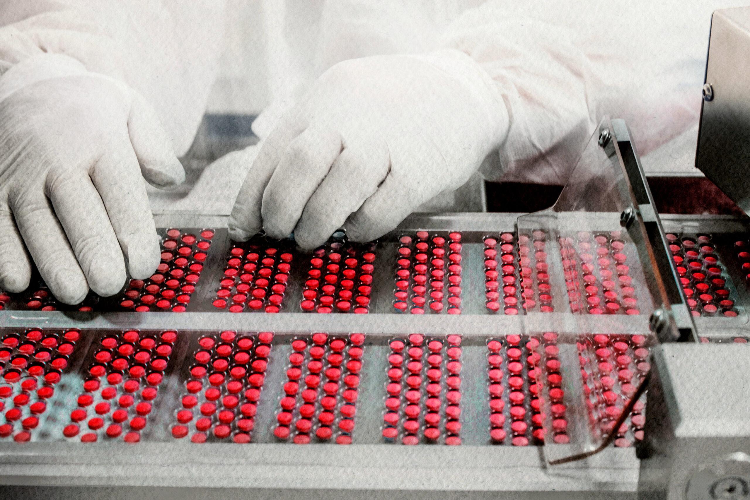 Worker inspecting pills on blisterpack conveyer belt